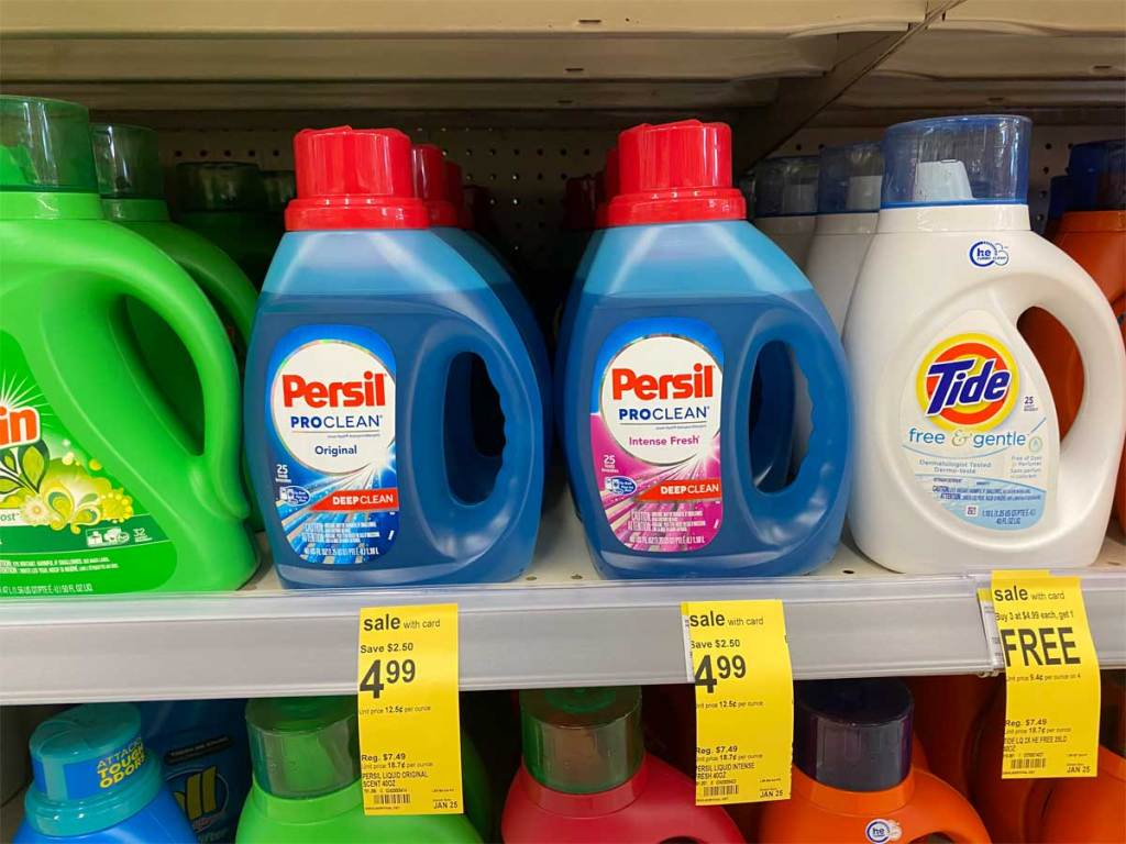 shelf of persil liquid laundry detergent on sale for $4.99 at walgreens with tide and gain laundry bottles next to it