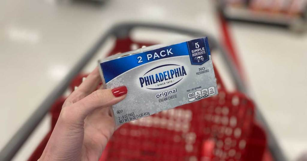 woman holding 2pack of philadelphia cream cheese in front of red shopping cart