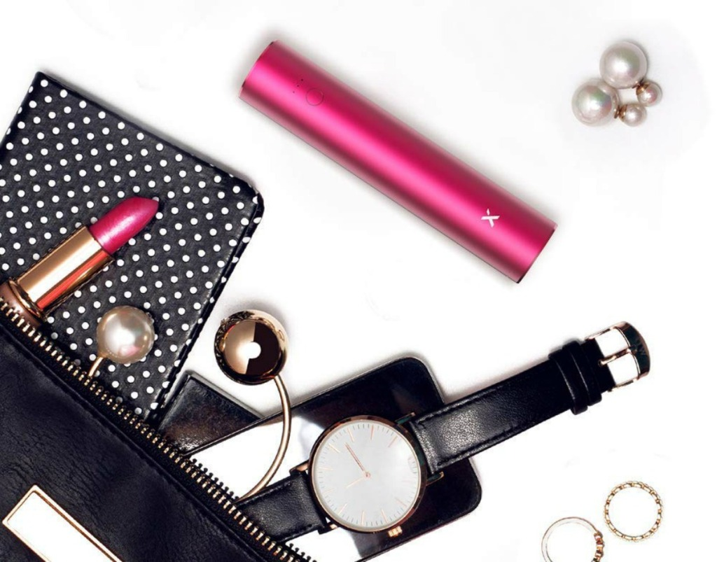 pink portable phone charger next to purse with contents spilling out