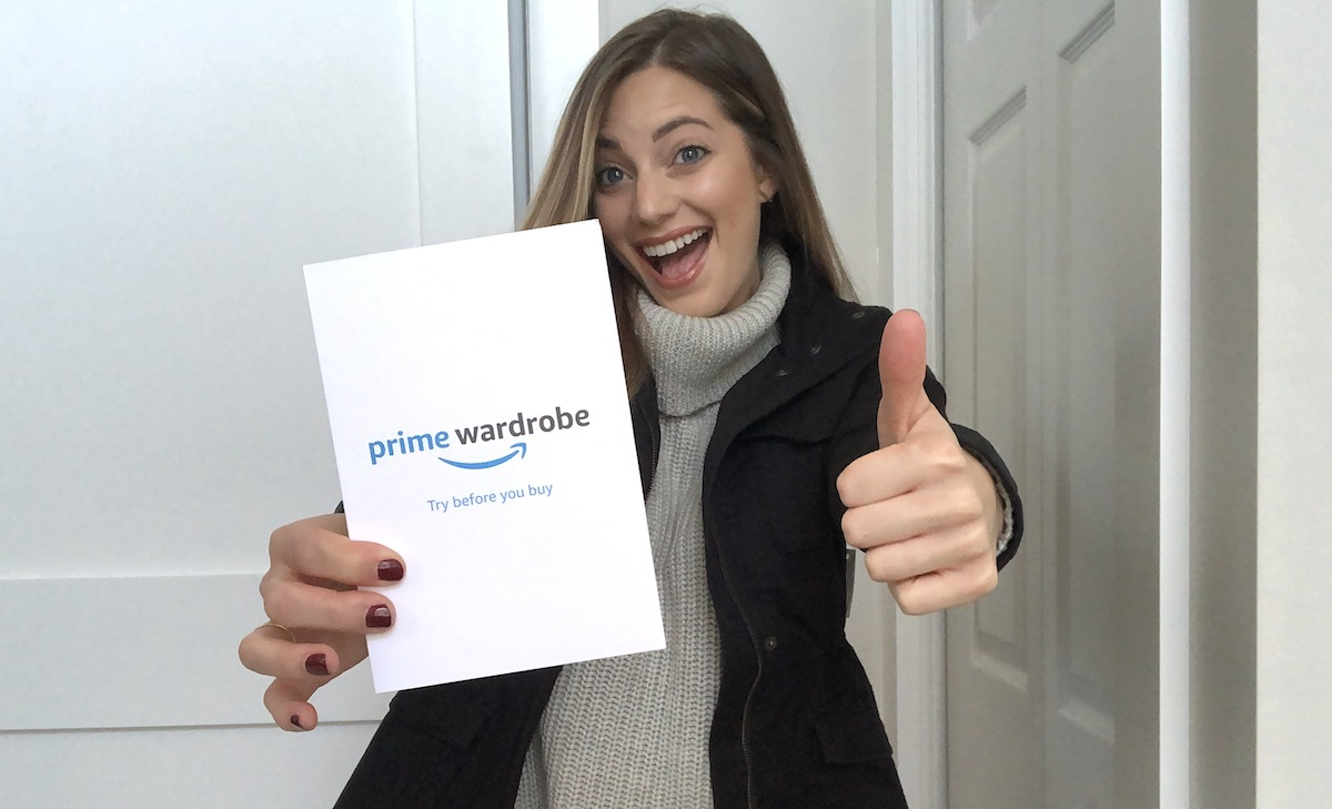 woman holding prime wardrobe card smiling with thumbs up