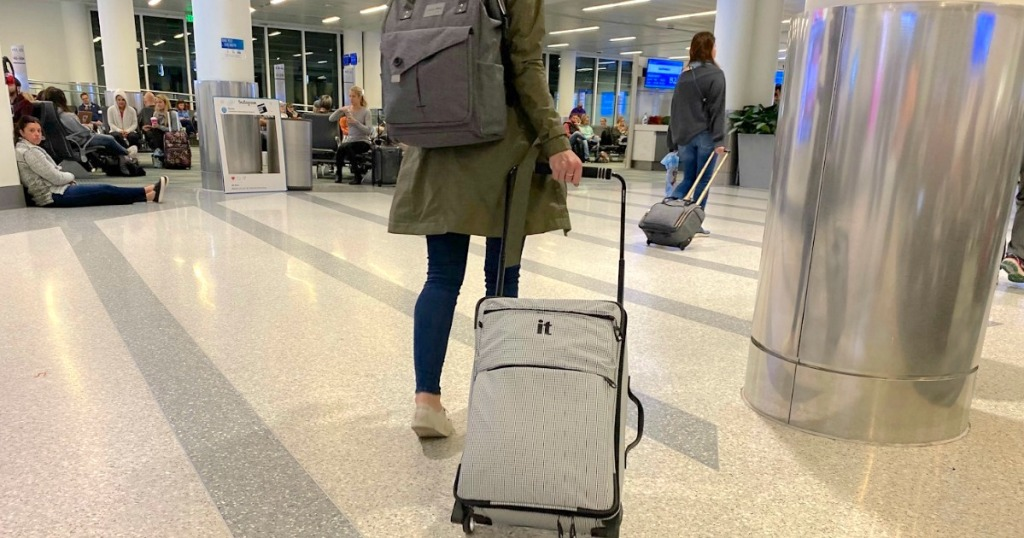 woman wearing backpack and pulling carryon luggage in airport