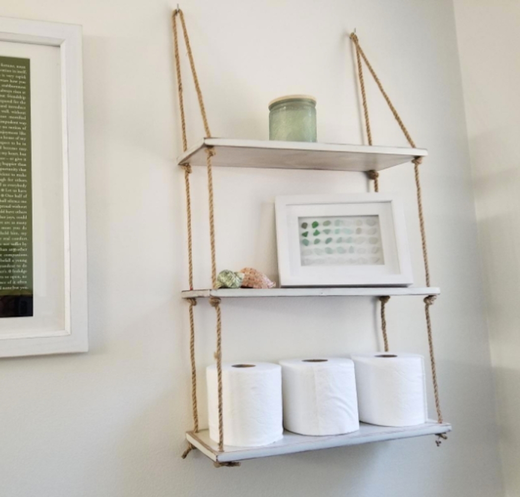hanging wood and rope shelf with bathroom decor hanging on wall