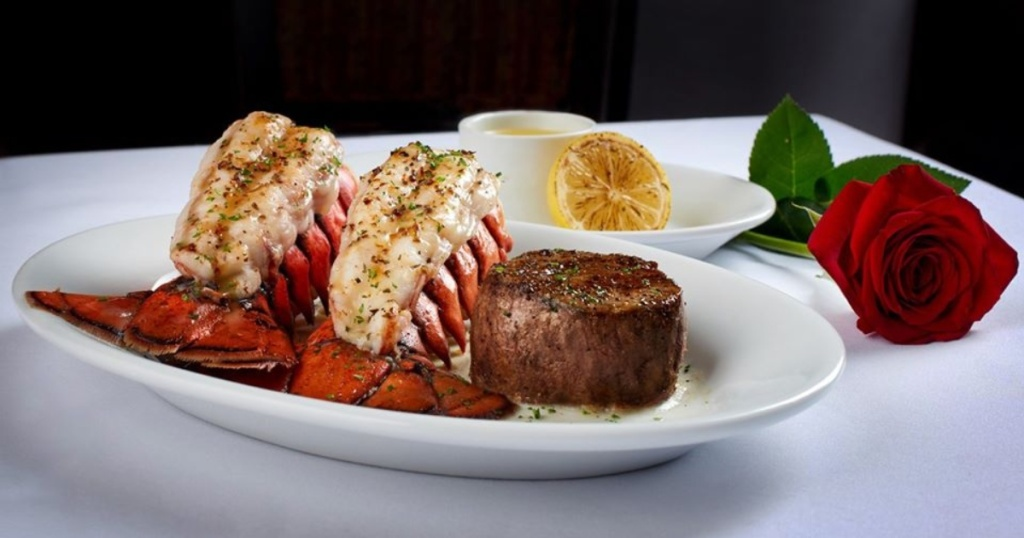 steak and lobster on a plate next to a rose