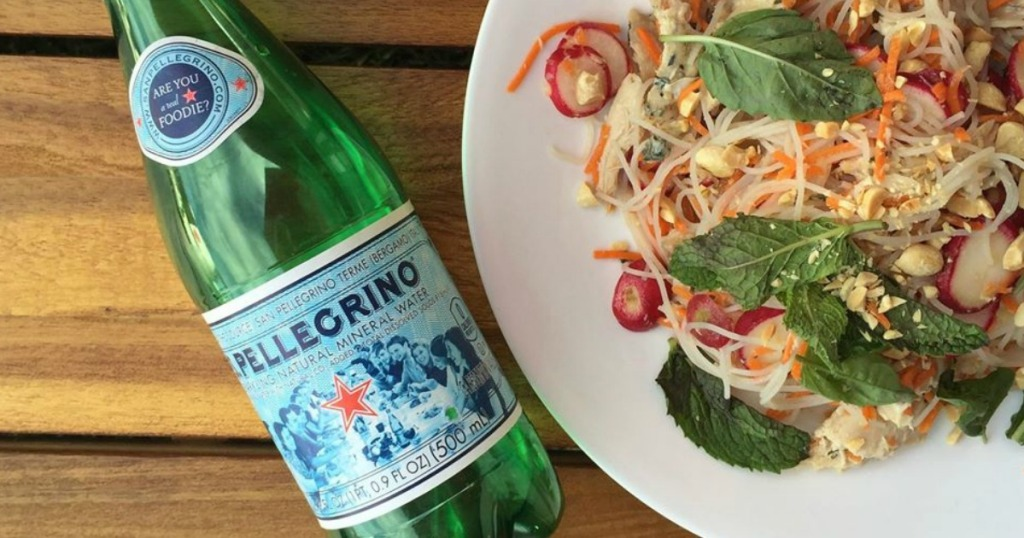 s. pellegrino bottled water next to a plate of rice noodles and vegetables