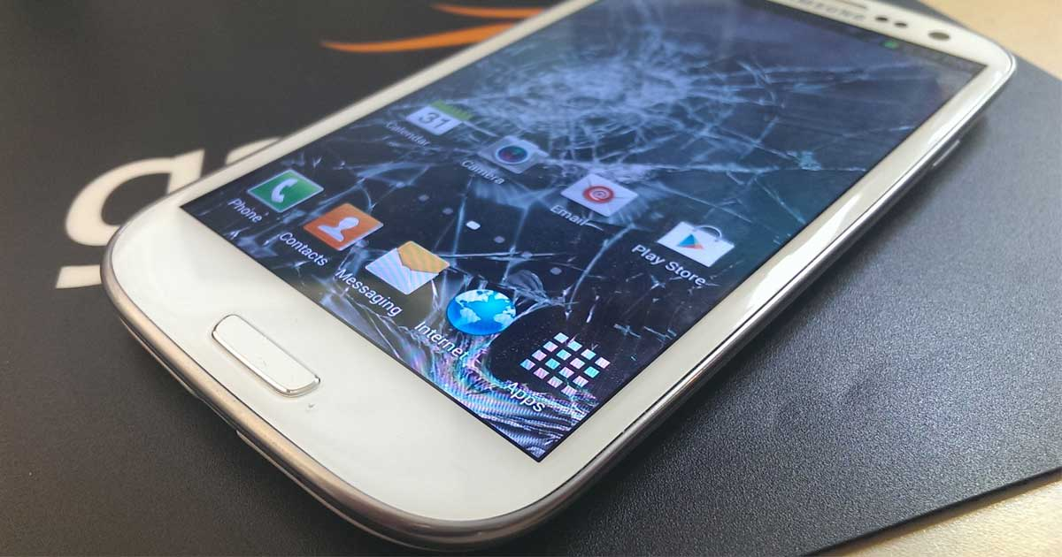 samsung galaxy phone laying on a table with a cracked screen