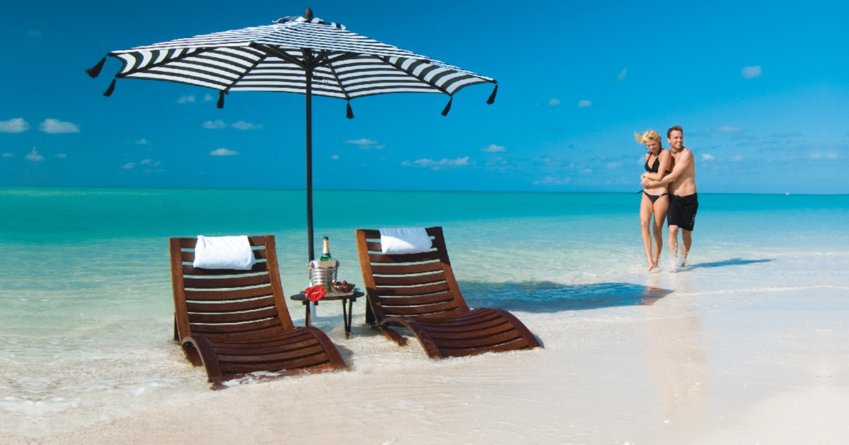 two chairs, and umbrella, and a couple on the beach