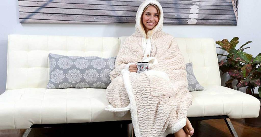 model sitting on a couch wearing Chic Home Design Hooded Snuggle Blanket