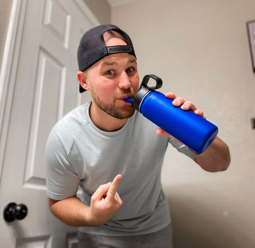 man sipping from straw on blue reusable water bottle