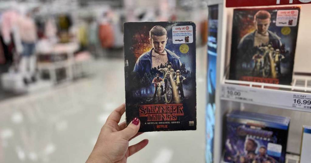 woman holding Stranger Things Seasons 1 & 2 DVD + Blu-ray, 4K UHD up in a store by the display