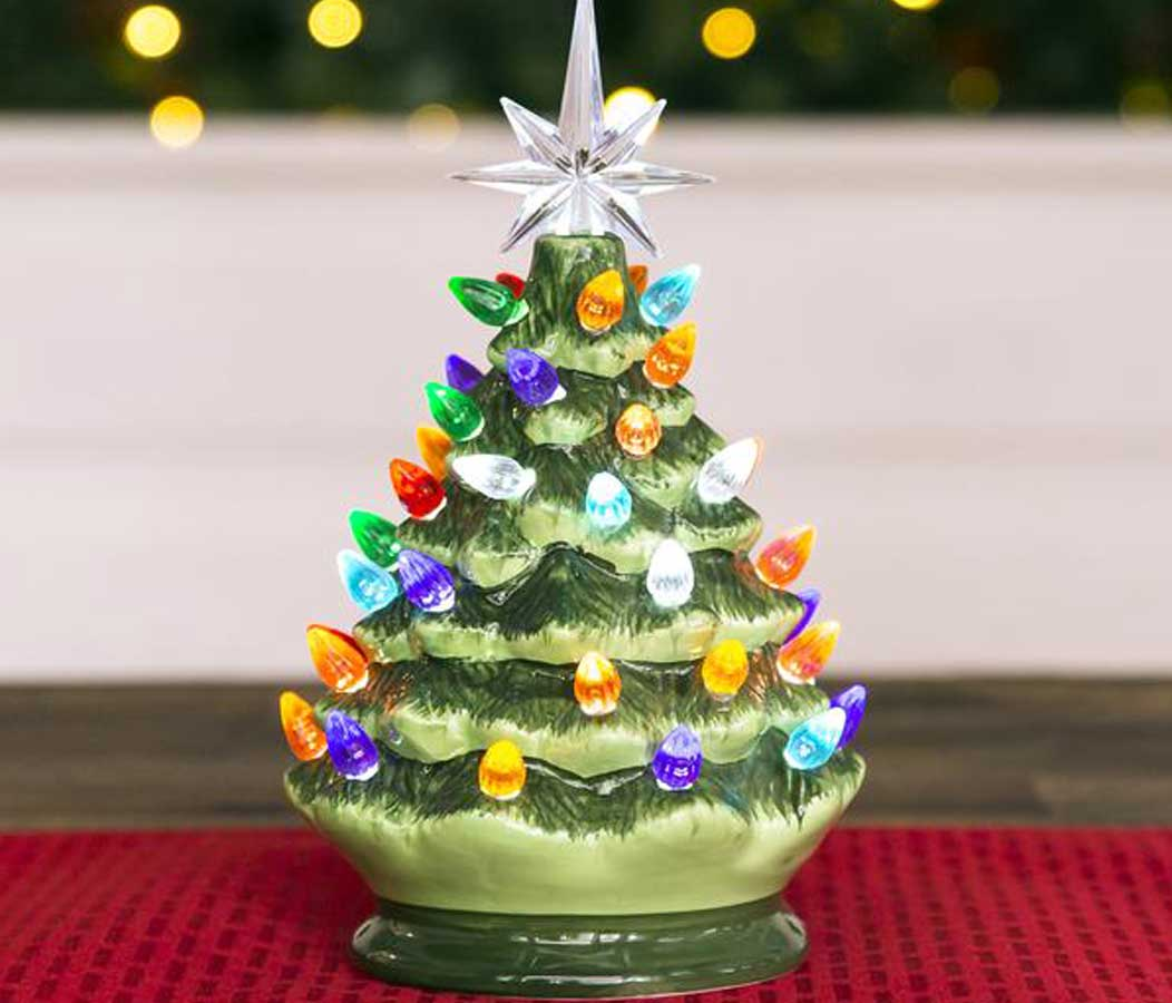 """9.5"""" Pre-Lit Hand-Painted Ceramic Tabletop Christmas Tree on a red table runner"""
