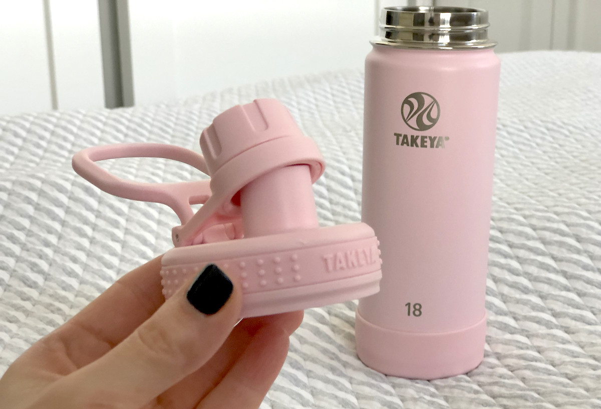 hand holding pink lid with takeya water bottle in background