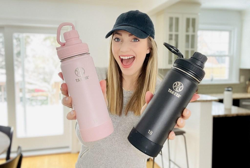 woman holding pink and black takeya water bottles