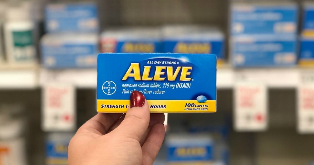 hand holding pain reliever caplets box in a store