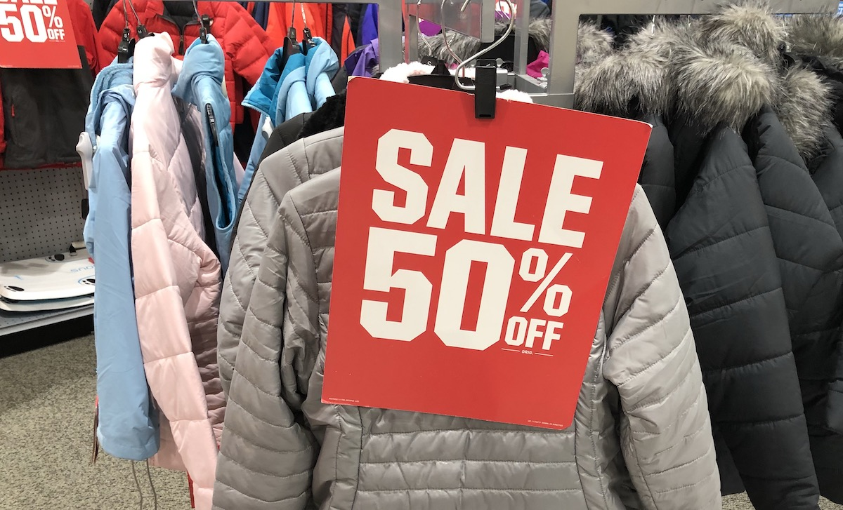 red and white sale 50% off sign hanging on rack of winter coats