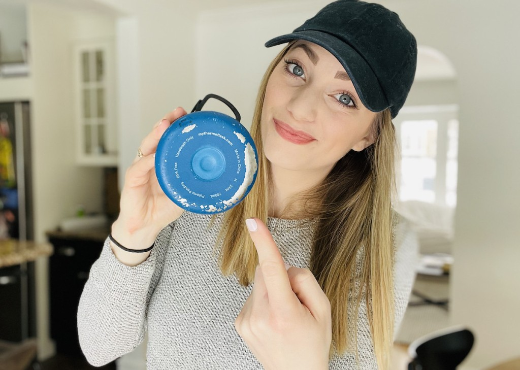 woman pointing at blue chipped water bottle