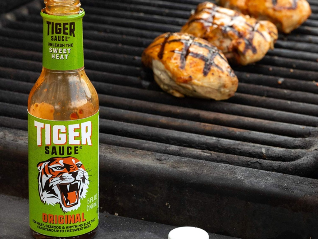 opened tiger sauce bottle in front of grill with chicken on grill