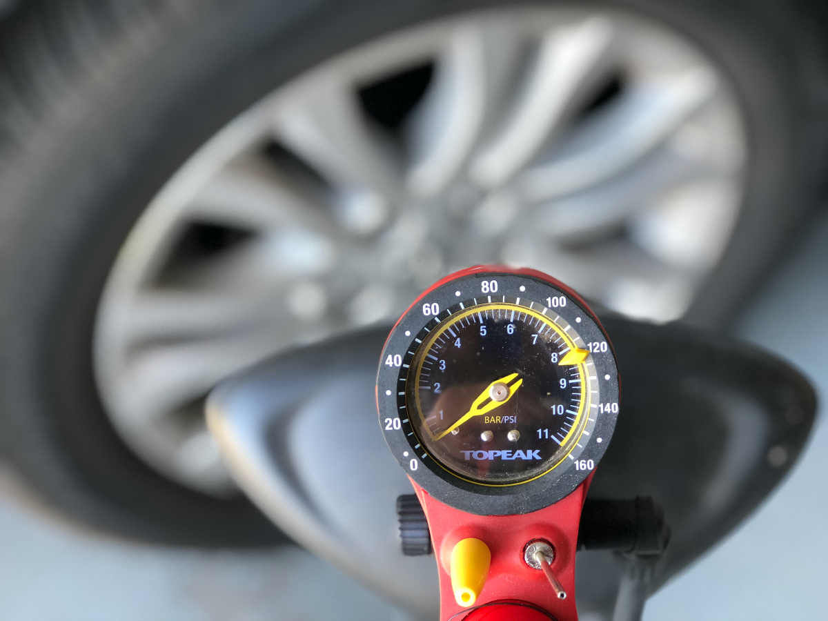 tire pressure gauge in front of car tire