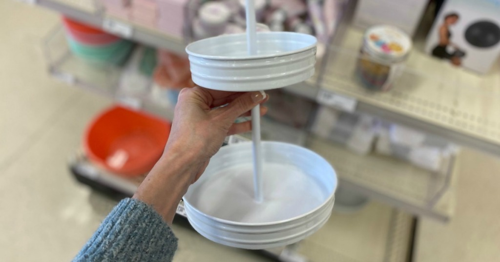 hand holding white two tiered metal serving tray in store