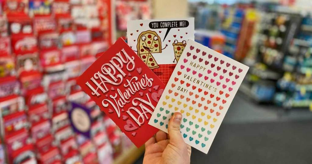 hand holding three Valentine's day cards in a store