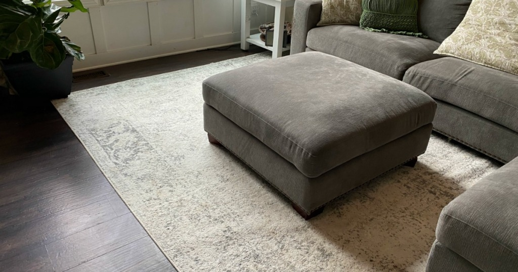 ottoman and couch in living space with large rug on floor