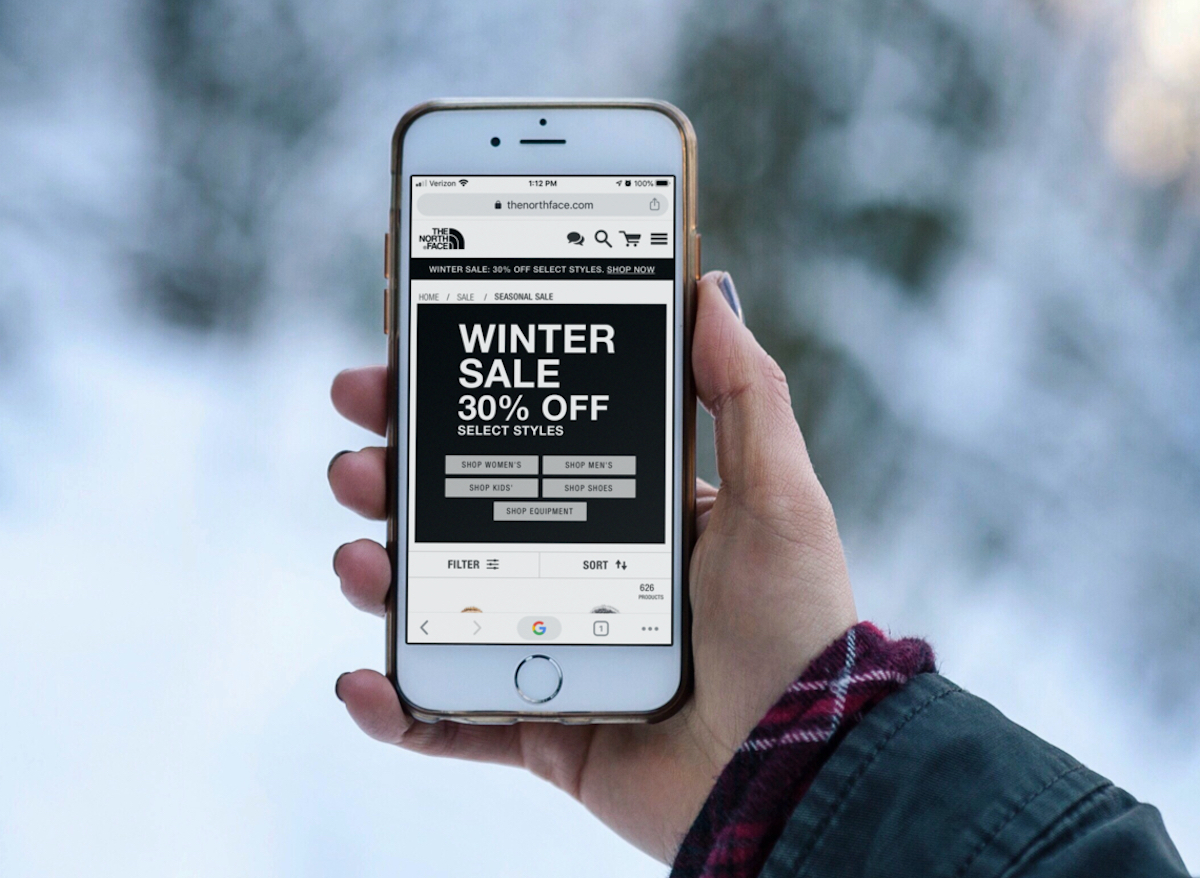 hand holding cell phone with winter sale on screen