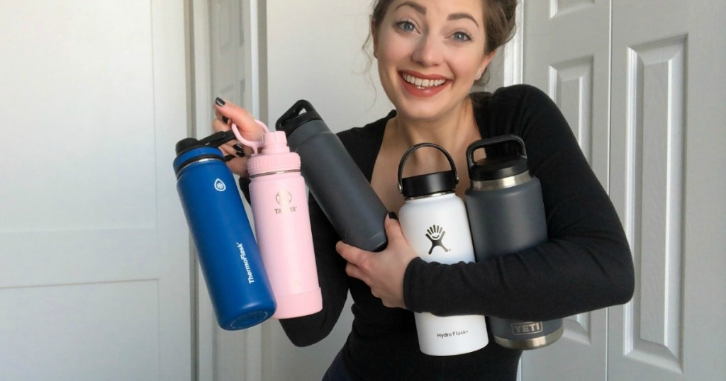 woman holding five water bottles
