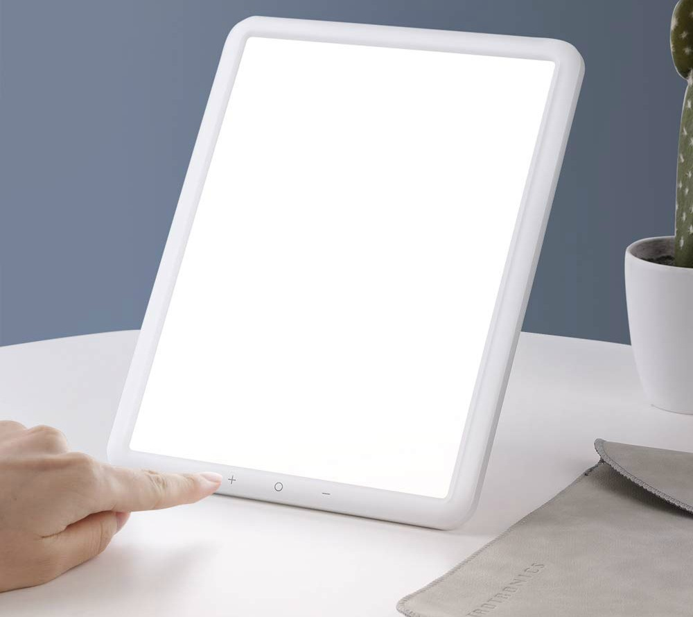woman pushing button on TaoTronics Light Therapy Lamp