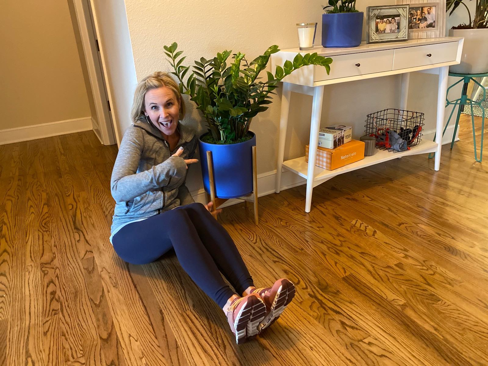 woman on the ground in home pointing at large potted plant