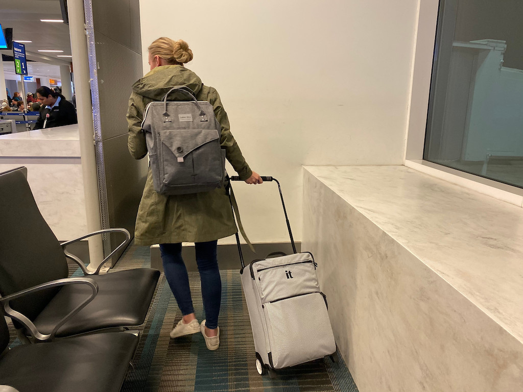 woman with bun and backpack pulling wheeled luggage in airport