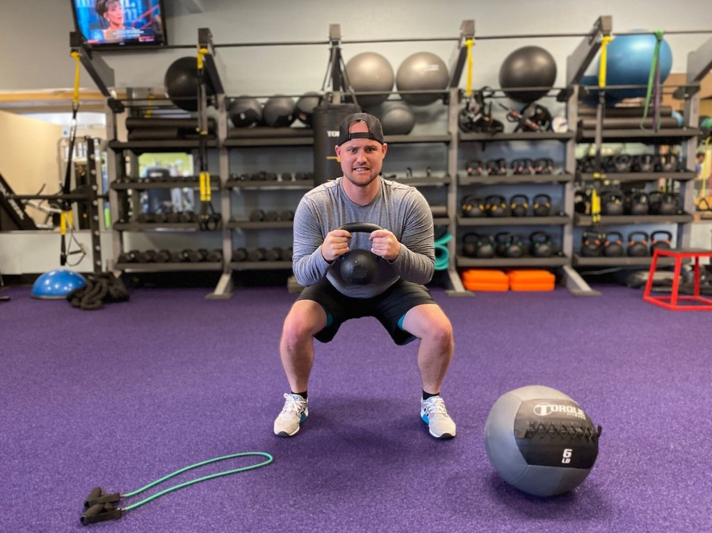 man doing a squat with kettlebell in purple gym