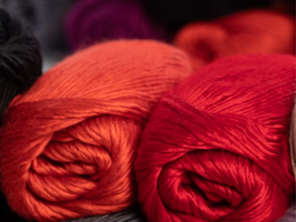 orange and red yarn thread spools