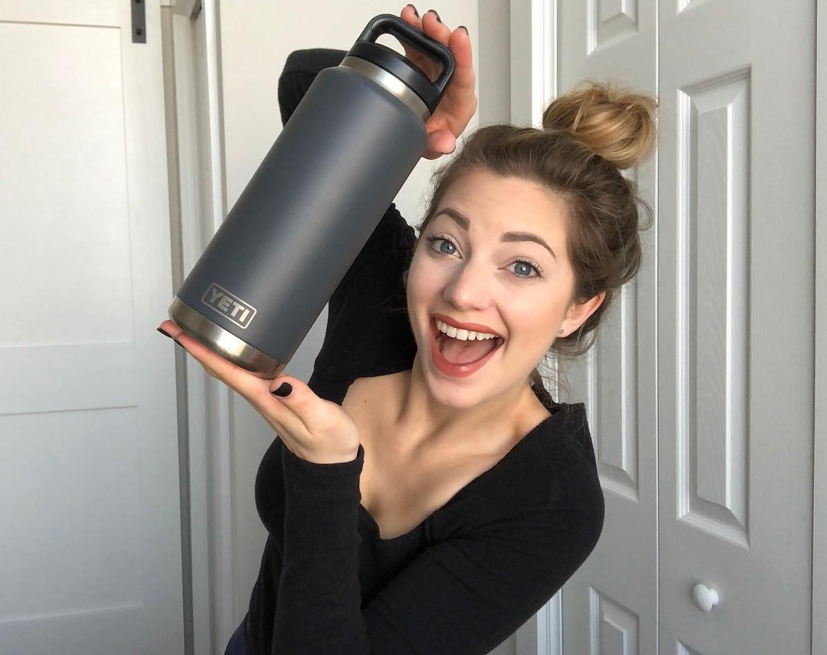 woman holding dark gray yeti water bottle