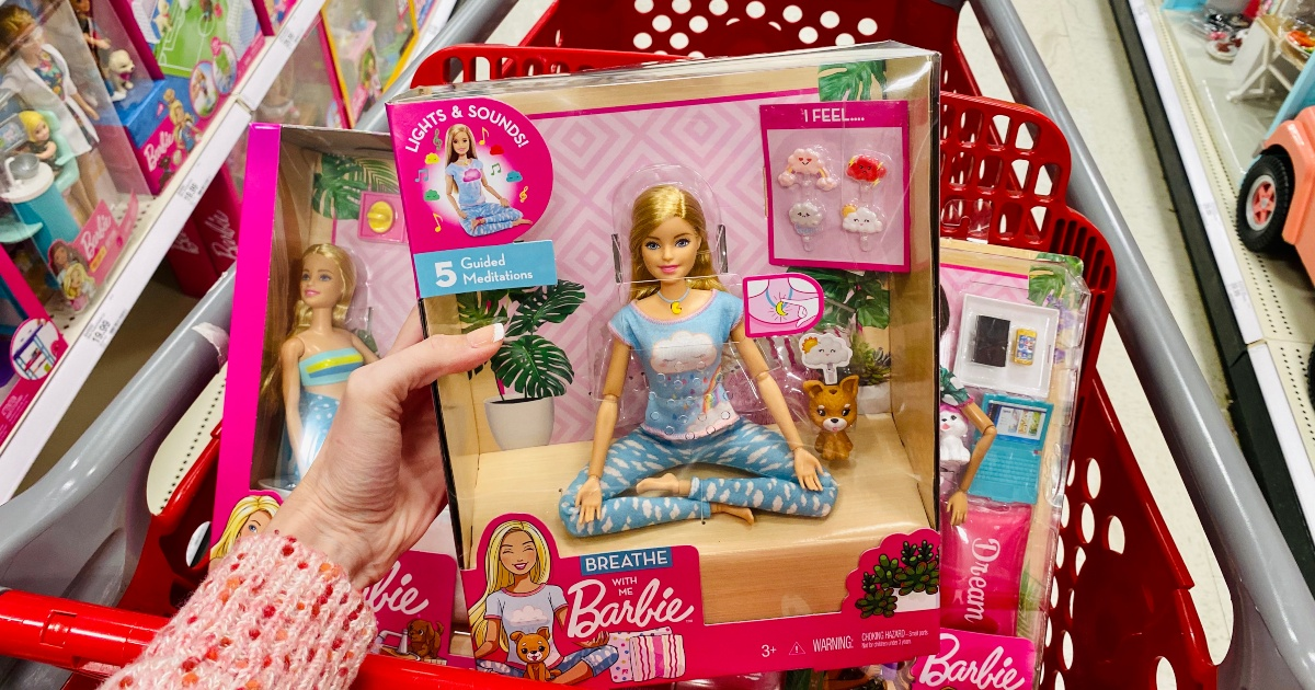 hand holding yoga Barbie package in front of Target cart