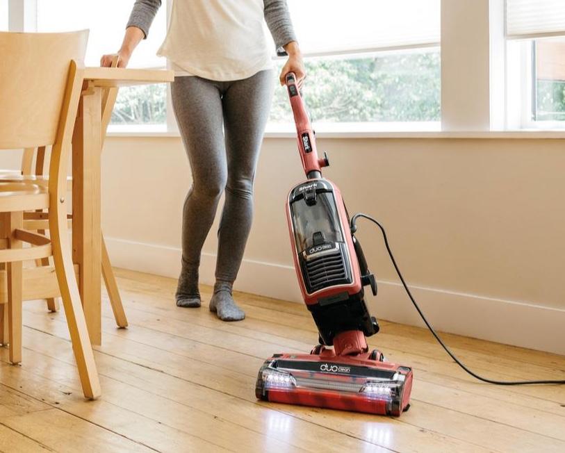 woman vacuuming hardwood floor near table with chairs