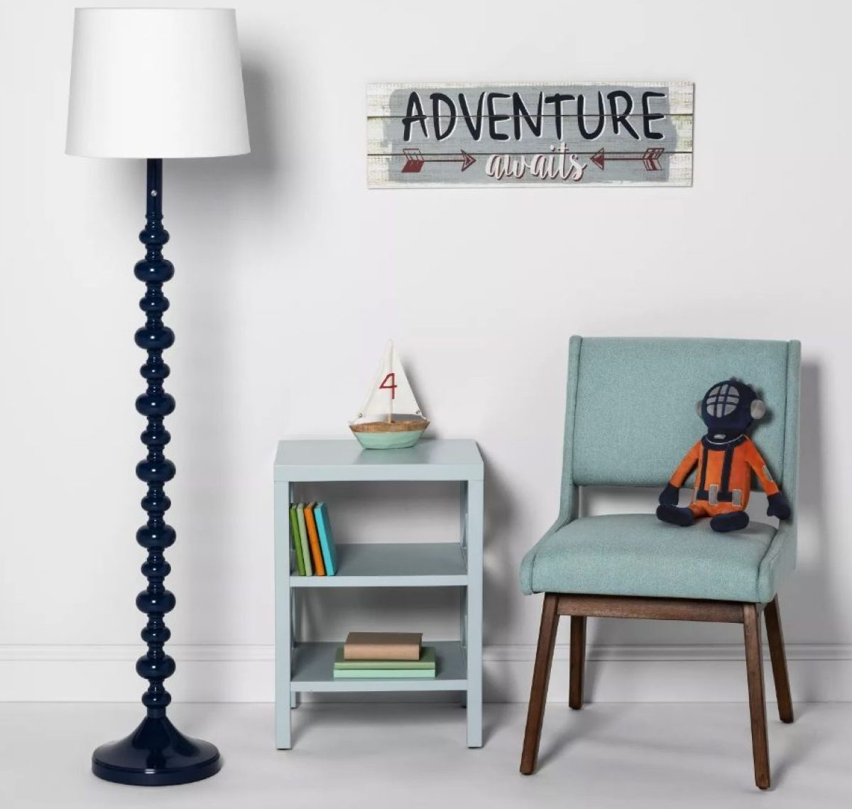 childrens room with lamp, small bookshelf with books, with sailboat on top, chair with monkey stuffed animal, and sign on wall