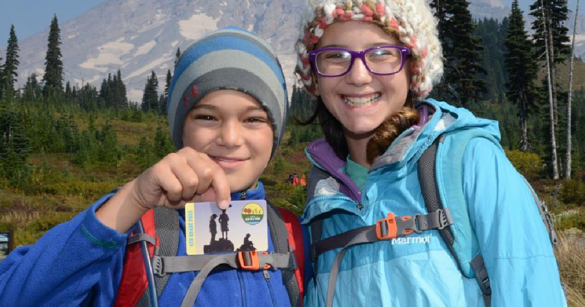 2 children standing next to each other wearng winter gear and one holding a park pass in his hand