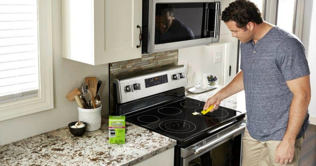 man in kitchen cleaning a stove