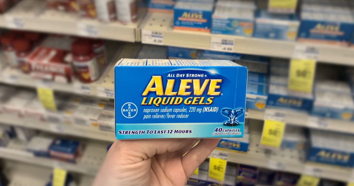 Hand holding Aleve in front of shelf