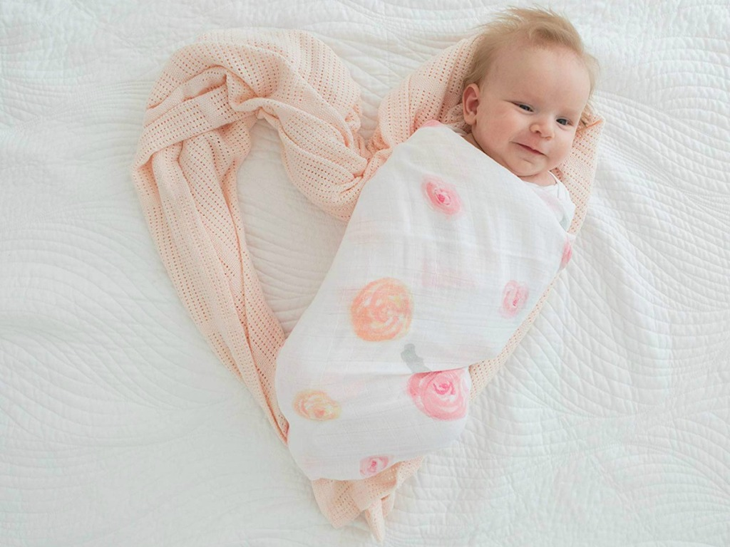 Baby wrapped in floral muslin blanket with additional blanket in heart shape