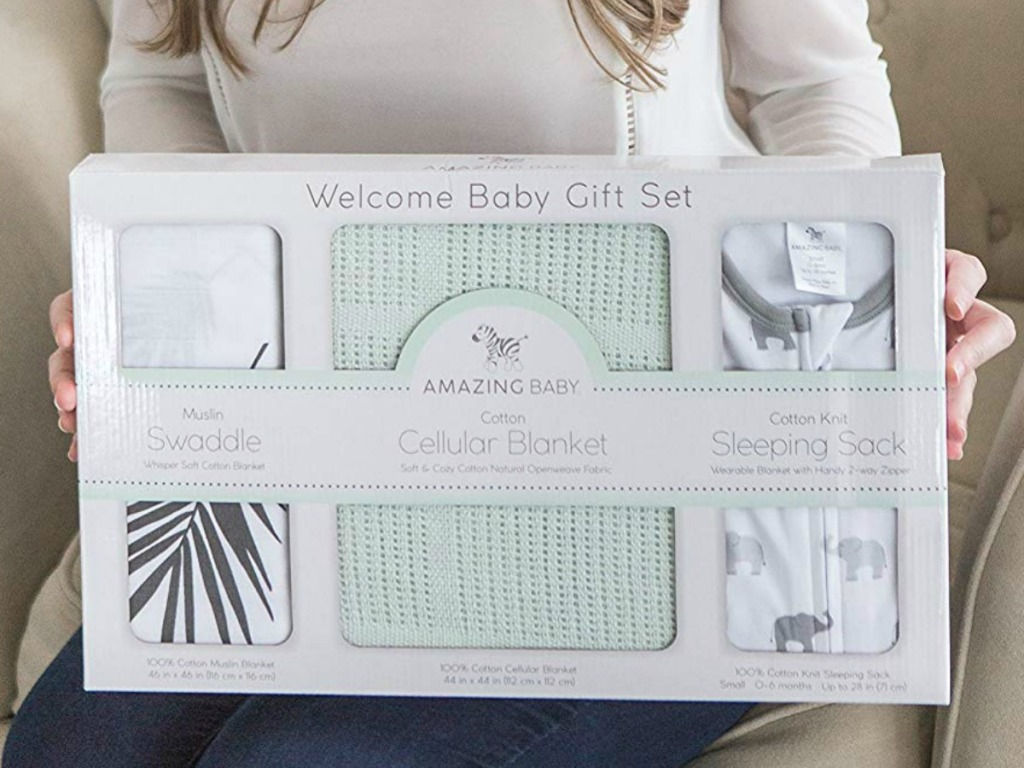 Woman holding a baby gift set with three blankets in packaging