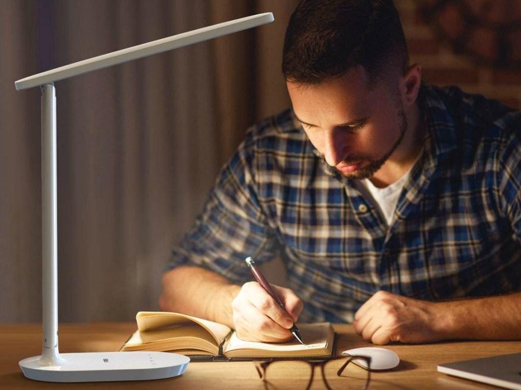Man sitting at desk using a portable LED lamp