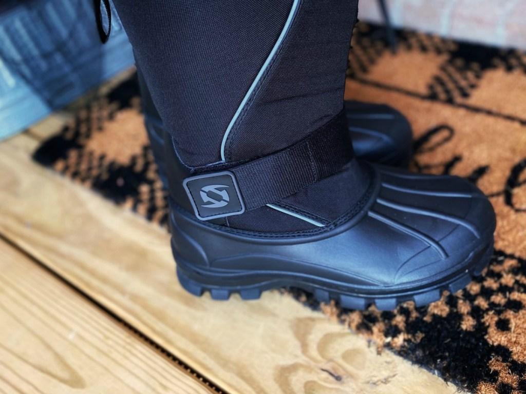 Men's black winter boots on doormat in front of doorway