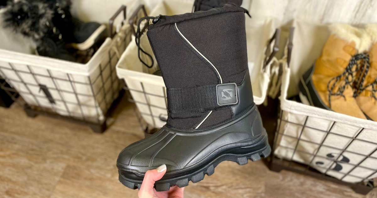 Woman holding a black winter boot for men