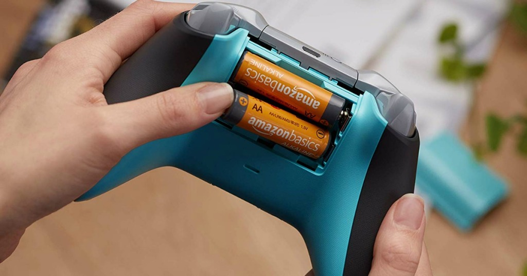 person putting 2 AA batteries into a video game controller