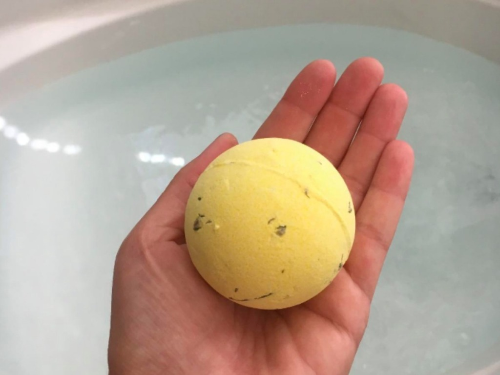 lady holding a bath bomb over a bathtub with water