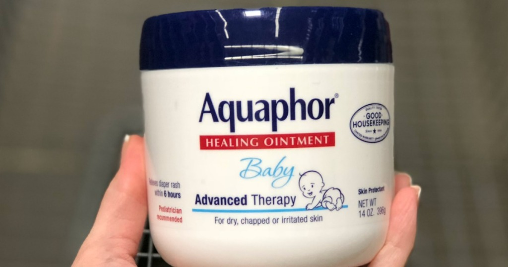 hand holding an Aquaphor Baby Healing Ointment Jar