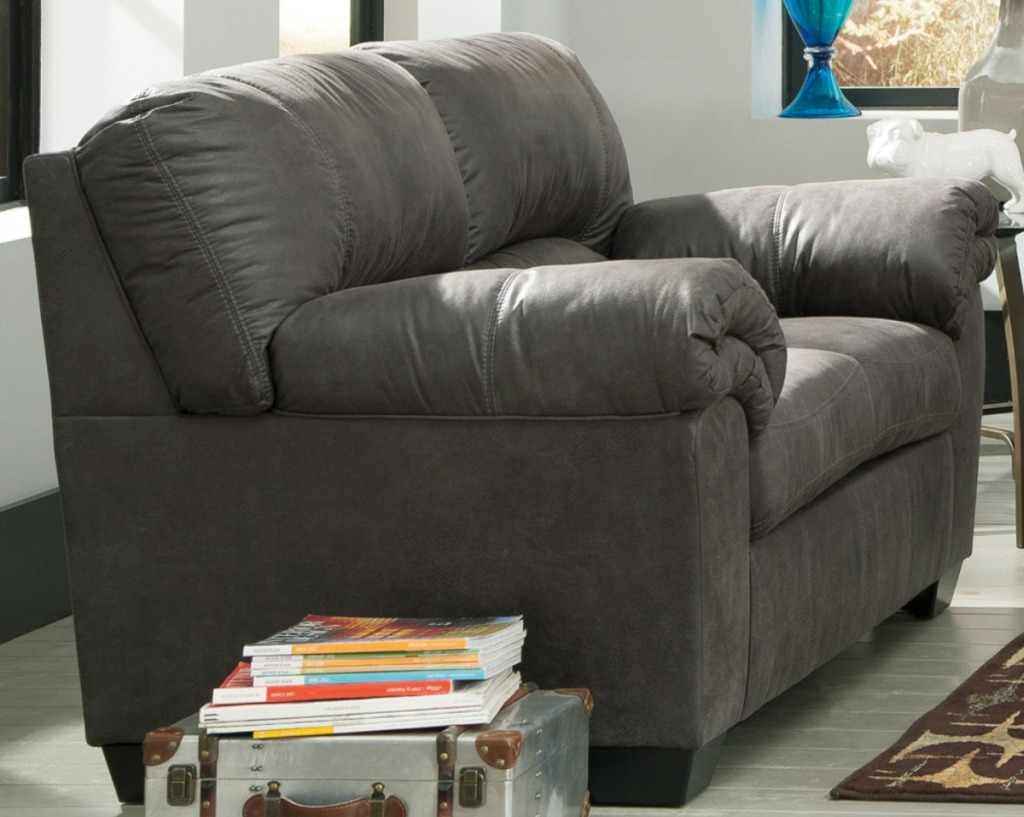 Large dark gray sofa in living room near storage trunk