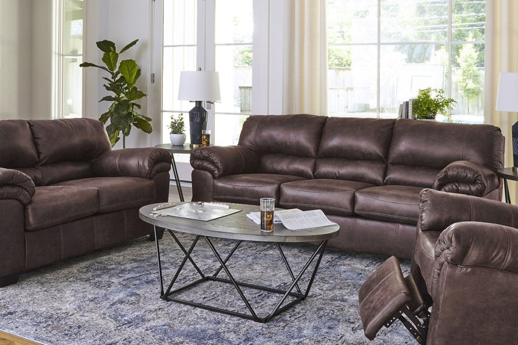 Large brown leather sofa in living room with matching loveseat an recliner chair