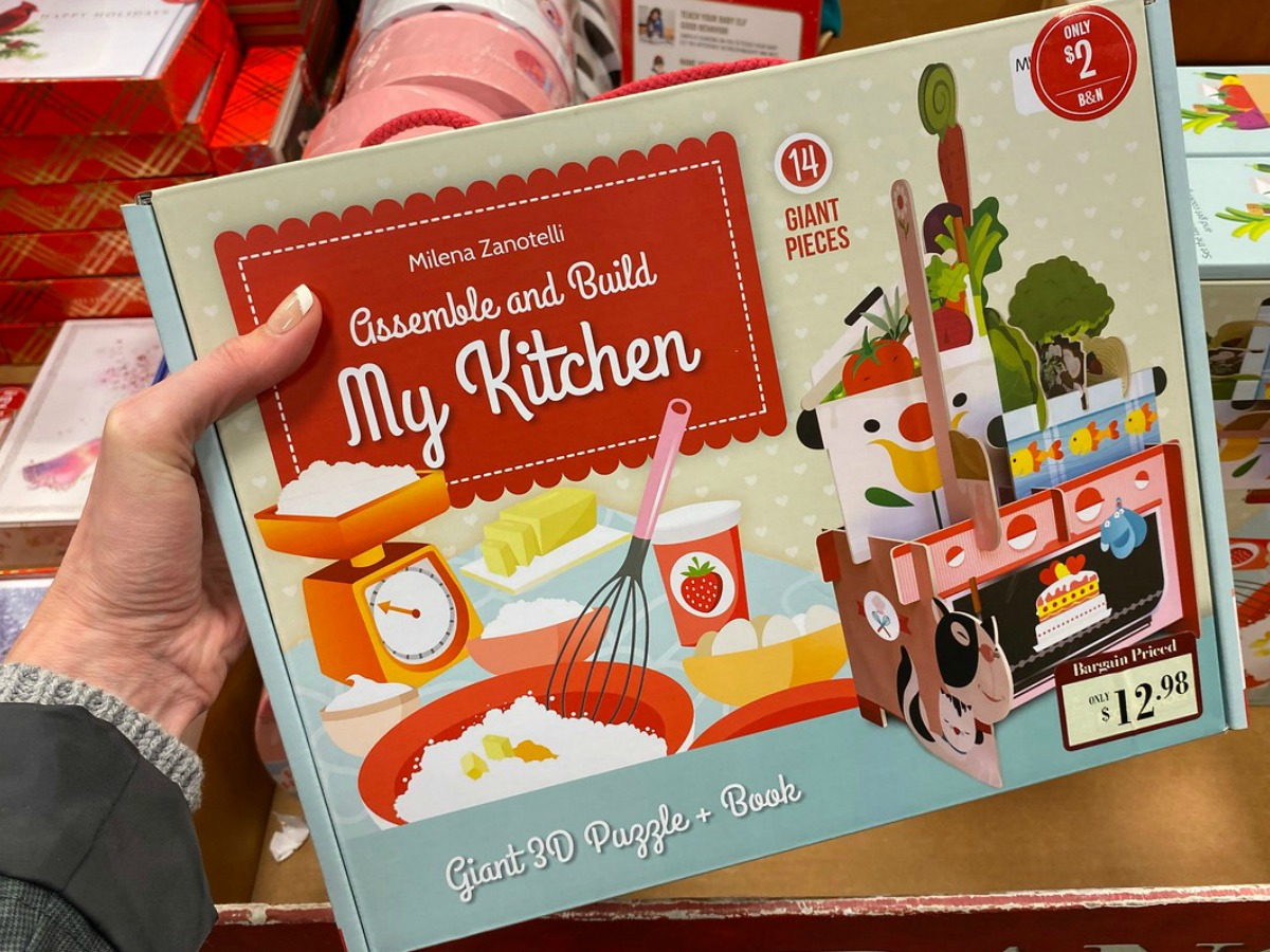 hand holding box with paper products for a kid to make a faux kitchen