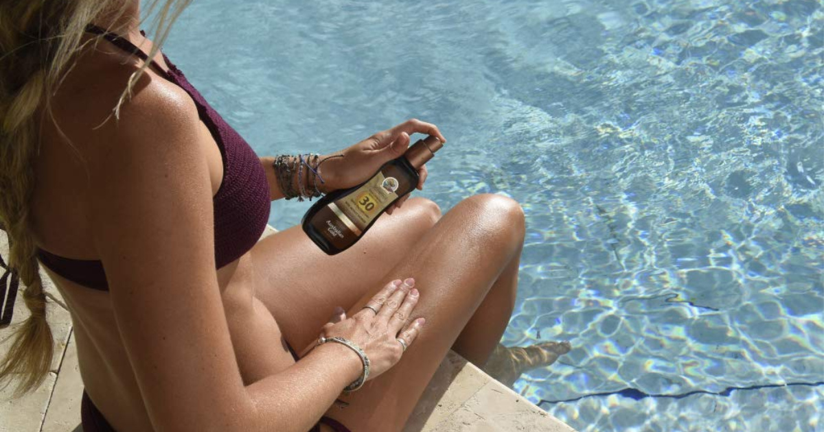 woman spraying Australian Gold Tanning Oil on her legs by the pool